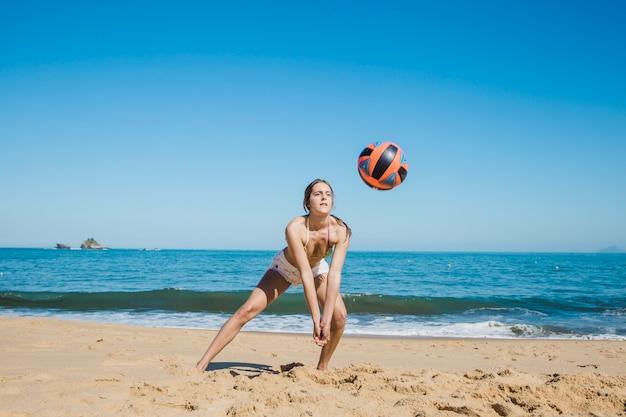 Mulher jogando praia volei em uma praia tropical