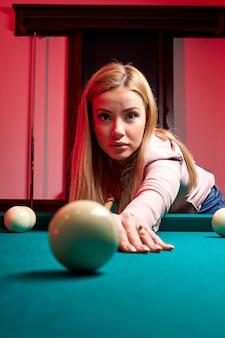 Mulher jogando sinuca, ela está com o objetivo de atirar a bola de sinuca, de mãos dadas na mesa de sinuca. bilhar