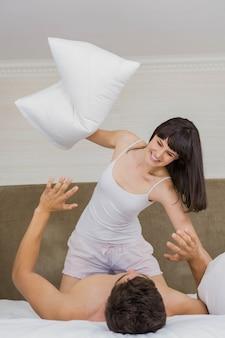 Mulher jogando travesseiro lutar com o homem na cama no quarto