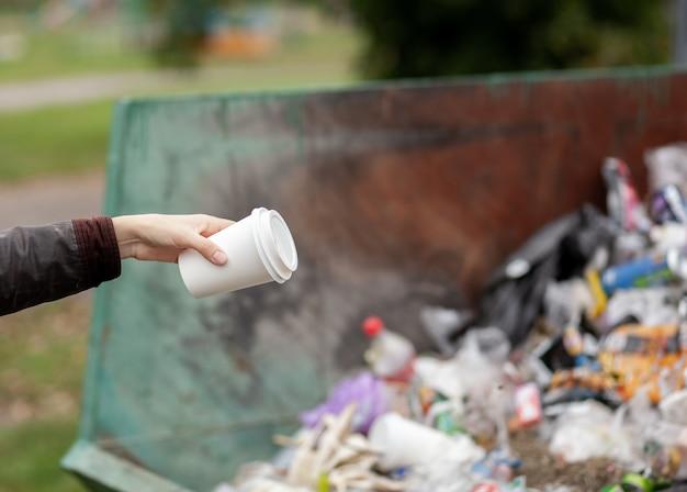 Mulher jogando um copo de papelão em uma lixeira. cuidando da limpeza da cidade e do meio ambiente. uma grande lixeira em um parque público