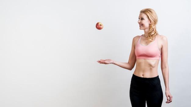 Mulher, jogando uma maçã