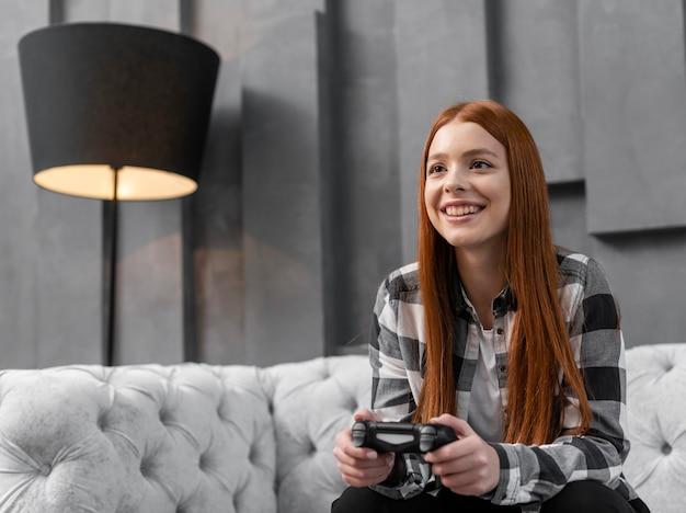 Mulher jogando videogame dentro de casa