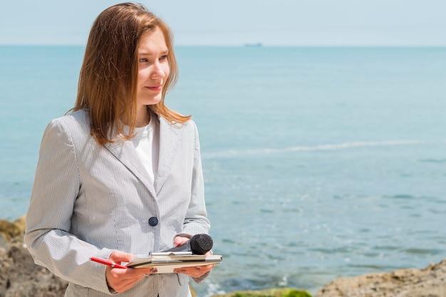 Mulher jornalista sendo no mar