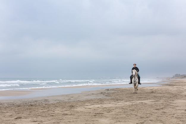 Mulher jovem a cavalo na praia em um dia nublado