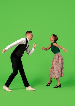 Mulher jovem à moda antiga dançando isolada sobre fundo verde