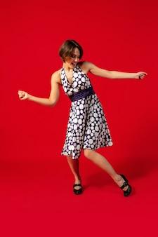 Mulher jovem à moda antiga dançando isolada sobre fundo vermelho
