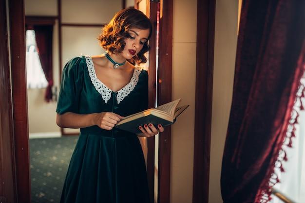 Mulher jovem à moda antiga viaja, compartimento de trem retrô. interior do velho vagão. viagem ferroviária, viagem de trem vintage