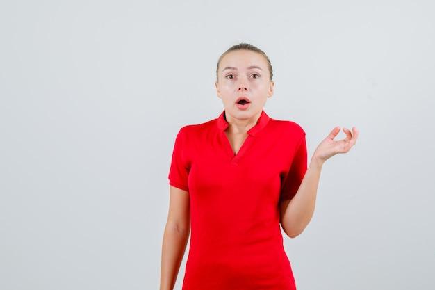 Mulher jovem a olhar para uma t-shirt vermelha e parecendo perplexa