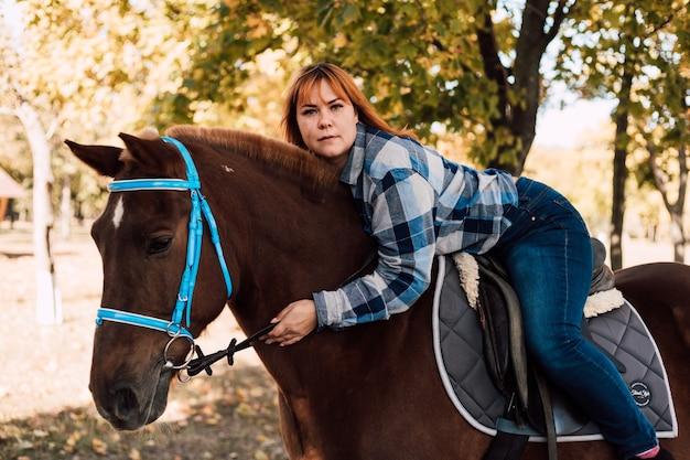 Mulher jovem abraça um cavalo caminhando no parque de outono em um dia ensolarado