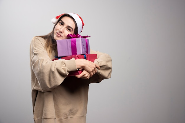 Mulher jovem abraçando dois presentes de natal