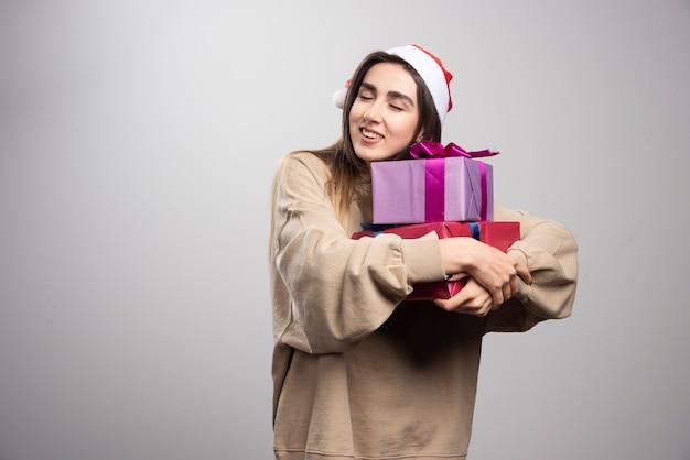 Mulher jovem abraçando duas caixas de presentes de natal.