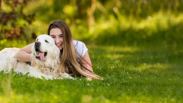 Mulher jovem abraçando seu cachorro com espaço de cópia