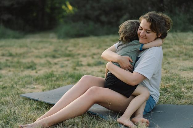 Mulher jovem abraçando seu filho em um dia ensolarado no prado