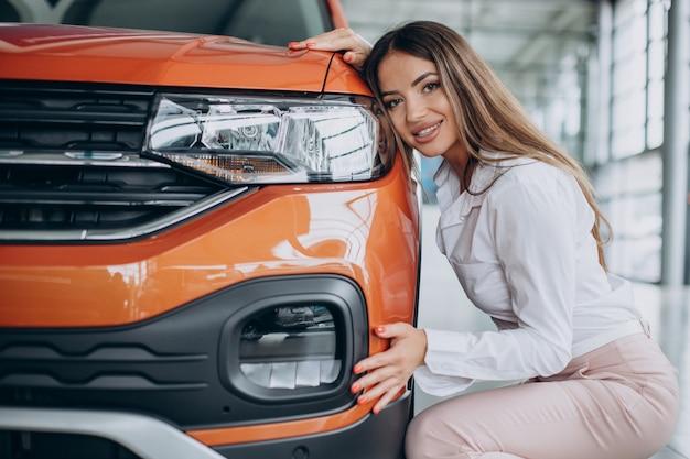 Mulher jovem abraçando seu novo carro