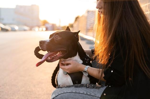 Mulher jovem abraçando seu pitbull