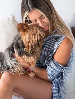 Mulher jovem abraçando um cachorro