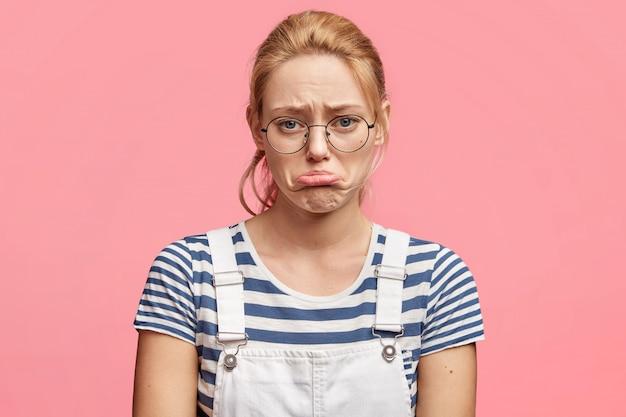 Mulher jovem abusada desesperada curva o lábio inferior em insatisfação, vestida casualmente, sente-se deprimida ao descobrir notícias trágicas, isolada sobre rosa