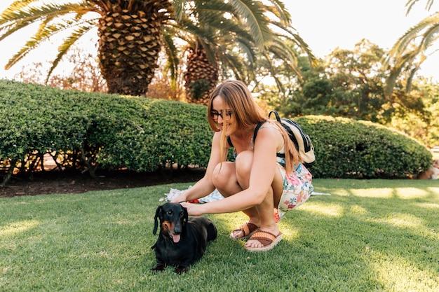 Mulher jovem, acariciar, dela, cão, parque