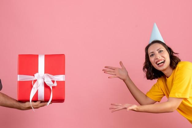 Mulher jovem aceitando presente de homem na mesa rosa emoção de ano novo mulher cor de festa de natal de frente