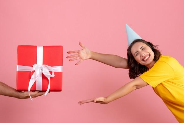 Mulher jovem aceitando um presente de homem no chão rosa emoção festa de natal cor de mulher de frente