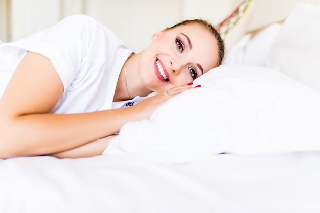 Mulher jovem acorda com um sorriso relaxando na cama durante a manhã