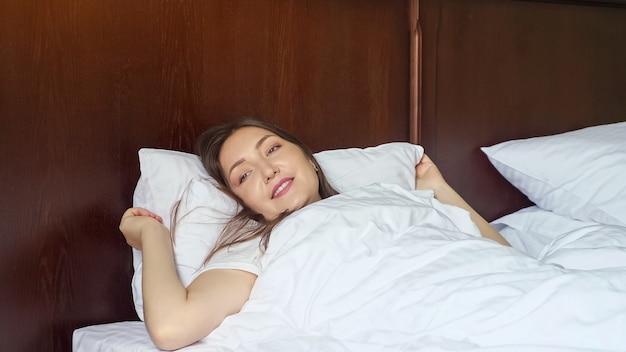Mulher jovem acorda e se espreguiça enquanto está deitada na cama