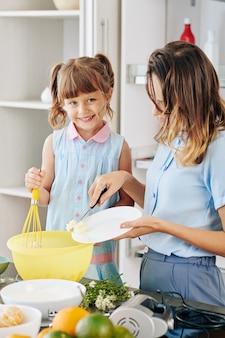Mulher jovem adicionando manteiga macia em uma tigela grande de plástico enquanto sua filha mistura ingredientes com um batedor