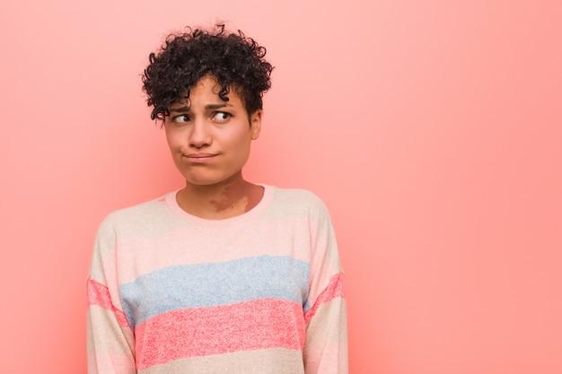 Mulher jovem adolescente americano africano misto confusa, sente-se duvidoso e inseguro.