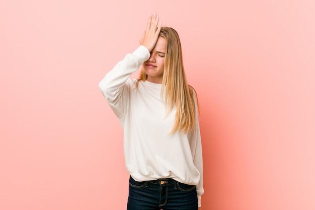 Mulher jovem adolescente loira esquecendo algo, tapa na testa com a palma da mão e fechar os olhos.