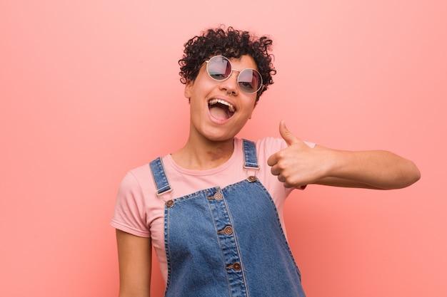 Mulher jovem adolescente sorrindo e levantando o polegar