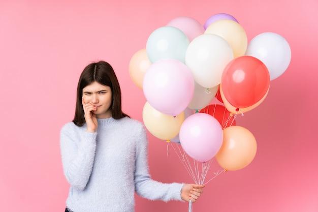 Mulher jovem adolescente ucraniana segurando muitos balões sobre parede rosa isolada, nervosa e assustada