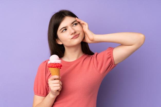 Mulher jovem adolescente ucraniano segurando um sorvete de corneta com dúvidas e com a expressão do rosto confuso