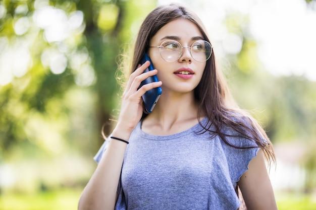 Mulher jovem adorável e feliz em pé e falando no celular na cidade