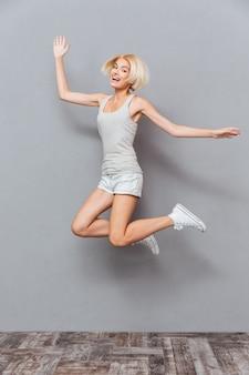 Mulher jovem adorável feliz rindo e pulando