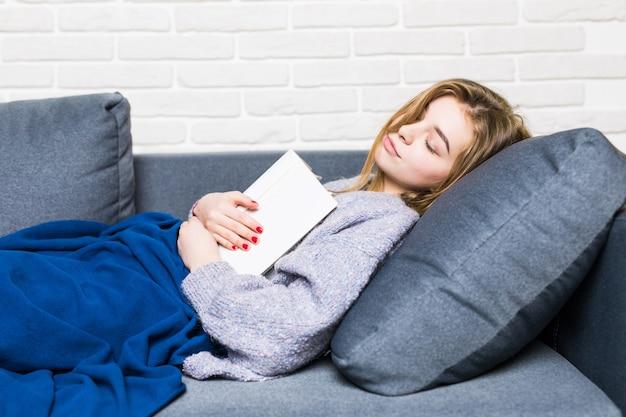 Mulher jovem adormecendo enquanto lia deitada de costas na cama com o livro apoiado no estômago