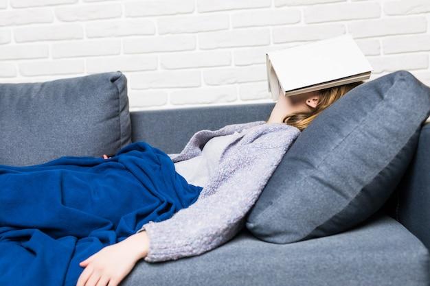 Mulher jovem adormecendo enquanto lia deitada no sofá com um livro na cabeça