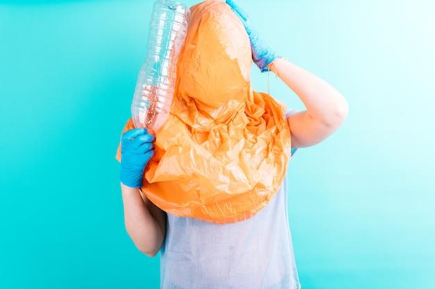 Mulher jovem adulta bonita com saco de reciclagem na cabeça, segurando uma garrafa de plástico. conceito engraçado. reciclando