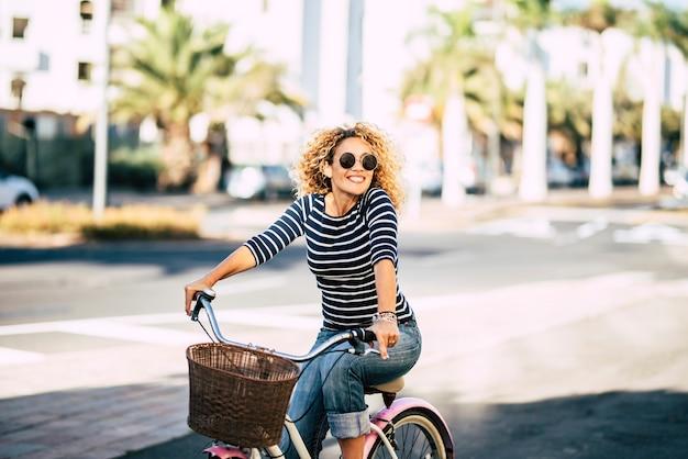 Mulher jovem adulta bonita e alegre desfrutar de um passeio de bicicleta na ensolarada atividade de lazer ao ar livre urbano na cidade - retrato de pessoas felizes - mulher na moda lá fora se divertindo