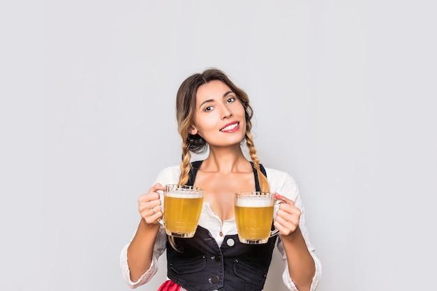 Mulher jovem adulta com canecas de cerveja nas mãos em um colete e roupas de blusa branca para a oktoberfest no estúdio