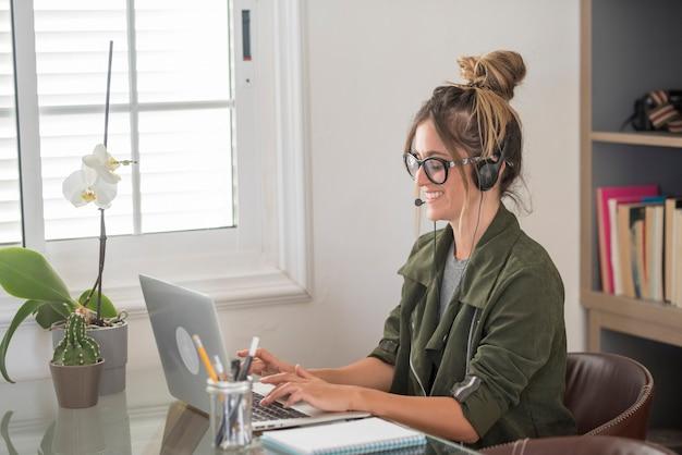 Mulher jovem adulta feliz em videoconferência em casa com estilo de vida de trabalho alternativo de trabalho inteligente e gratuito
