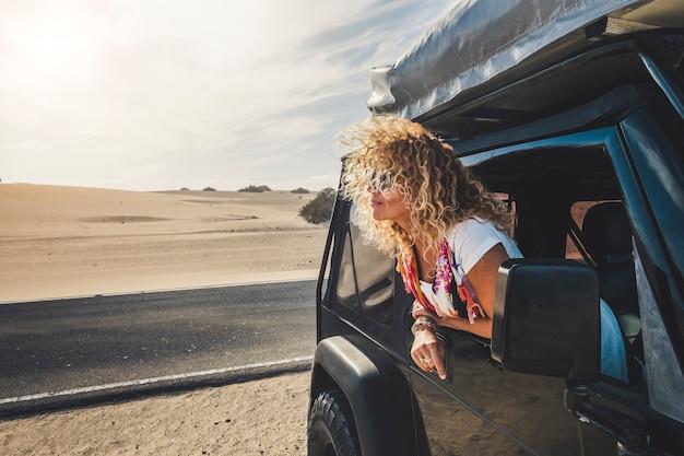 Mulher jovem adulta linda loira de cabelo encaracolado fora do carro curtindo o estilo de vida de viagens e alternatie férias com barraca no telhado e acampamento grátis em todos os lugares - pessoas viajando - retorno do deserto