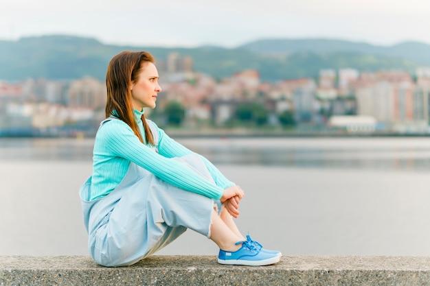 Mulher jovem adulta milenar apreciando a luz do sol, olhando para a paisagem sentada na parede