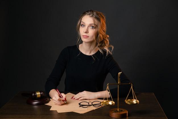 Mulher jovem advogada em um vestido formal, sentada à mesa e escrevendo algo à caneta.