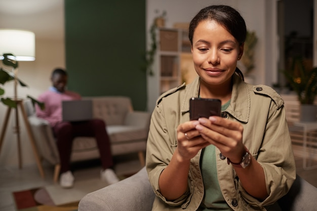 Mulher jovem africana assistindo algo em seu telefone celular com um homem trabalhando em um laptop no fundo do escritório