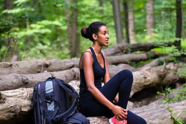 Mulher jovem africana, caminhadas na trilha da floresta
