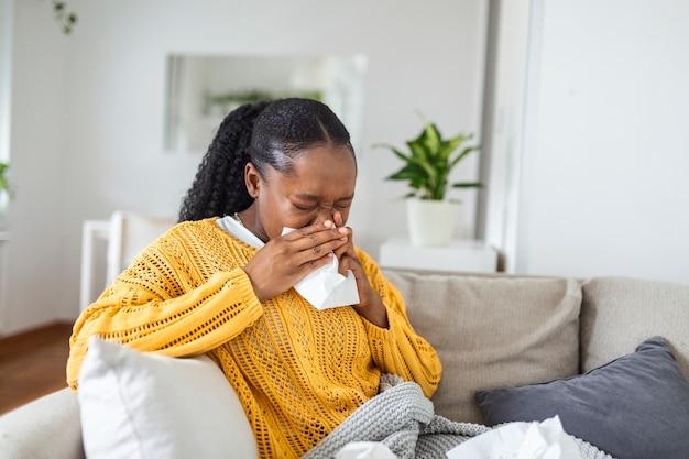 Mulher jovem africana doente coberta com um cobertor, assoando o nariz, pegou febre, pegou resfriado, espirrando em tecido, sente-se no sofá, garota negra alérgica doente com sintomas de alergia, tosse em casa, conceito de gripe