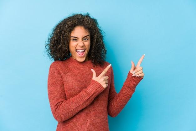 Mulher jovem afro-americana de cabelo encaracolado, apontando com os indicadores para um espaço de cópia, expressando entusiasmo e desejo.