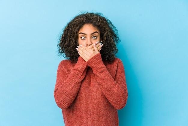 Mulher jovem afro-americana de cabelo encaracolado chocada, cobrindo a boca com as mãos.