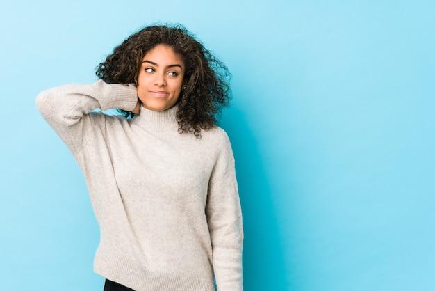 Mulher jovem afro-americana de cabelo encaracolado tocando a nuca, pensando e fazendo uma escolha.