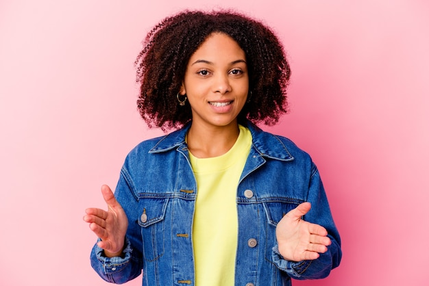Mulher jovem afro-americana de raça mista isolada segurando algo com as duas mãos, apresentação do produto.